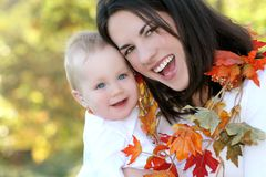 Madre y bebé con las hojas - tema de la caída Fotos de archivo