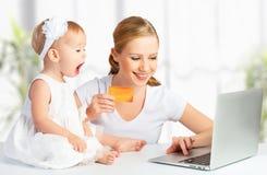 Madre y bebé con un ordenador portátil y una tarjeta de crédito Foto de archivo