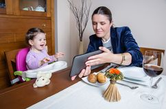 Madre y bebé de la empresaria que miran la tableta Foto de archivo libre de regalías