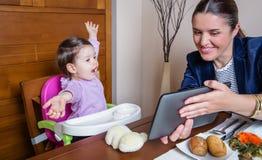 Madre y bebé de la empresaria que miran la tableta Imagenes de archivo