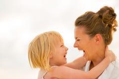 Madre y bebé de risa que abrazan en la playa Imagen de archivo libre de regalías