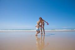 Madre y bebé de risa que corren en la orilla Imagen de archivo
