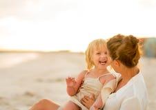Madre y bebé de risa que se sientan en la playa Fotos de archivo