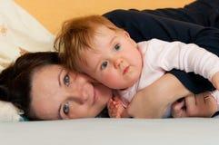 Madre y bebé en cama fotos de archivo