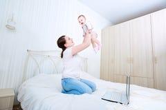 Madre y bebé en cama Niño y padre junto en casa M joven foto de archivo