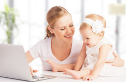 Madre y bebé en casa usando el ordenador portátil foto de archivo