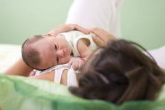 Madre y bebé en dormitorio verde Imagen de archivo libre de regalías