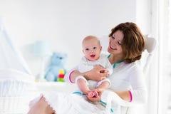 Madre y bebé en el dormitorio blanco Fotografía de archivo libre de regalías