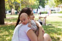 Madre y bebé en el parque público, madre cariñosa que cuida al niño lindo en las manos para eructar después de amamantar, reclina imagen de archivo