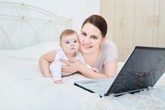 Madre y bebé en la sonrisa del dormitorio Fotos de archivo