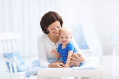 Madre y bebé en la tabla cambiante foto de archivo