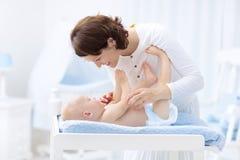 Madre y bebé en pañal en la tabla cambiante Fotos de archivo libres de regalías