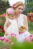 Madre y bebé en rosaleda Imagen de archivo