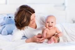 Madre y bebé en una cama blanca Imagenes de archivo