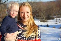 Madre y bebé felices afuera en invierno Fotos de archivo