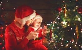 Madre y bebé felices de la familia cerca del árbol de navidad en día de fiesta cerca Imagen de archivo