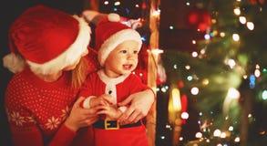 Madre y bebé felices de la familia cerca del árbol de navidad en día de fiesta cerca Fotografía de archivo