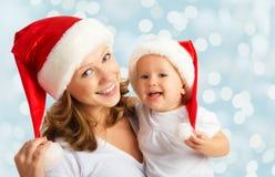 Madre y bebé felices de la familia en sombreros de la Navidad imagenes de archivo