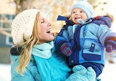 Madre y bebé felices en parque del invierno Foto de archivo libre de regalías