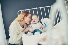 Madre y bebé jovenes en jugar de la cama Fotos de archivo libres de regalías