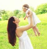 Madre y bebé jovenes felices junto al aire libre en verano soleado Imagen de archivo libre de regalías