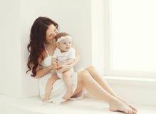 Madre y bebé jovenes felices junto en casa en el sitio blanco Fotos de archivo libres de regalías