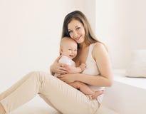 Madre y bebé jovenes felices junto en casa en pizca Imagen de archivo libre de regalías
