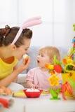 Madre y bebé que comen el huevo de Pascua Foto de archivo libre de regalías