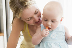 Madre y bebé que comen la zanahoria Fotografía de archivo libre de regalías