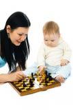 Madre y bebé que juegan a ajedrez Fotos de archivo libres de regalías