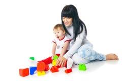 Madre y bebé que juegan con el juguete de las unidades de creación Foto de archivo