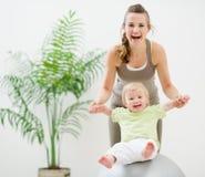 Madre y bebé que juegan con la bola de la aptitud Fotografía de archivo libre de regalías