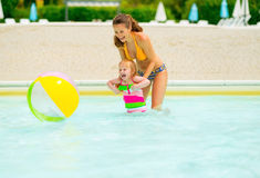 Madre y bebé que juegan con la pelota de playa en piscina Fotografía de archivo