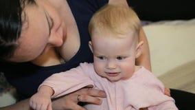 Madre y bebé que juegan y que sonríen en casa almacen de video