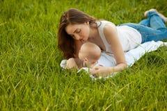 Madre y bebé que mienten en la hierba verde al aire libre Foto de archivo
