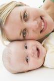 Madre y bebé que mienten en suelo