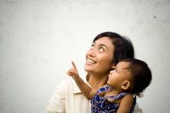 Madre y bebé que miran para arriba y que señalan Foto de archivo libre de regalías