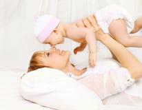 madre y bebé que se divierten en casa en la cama Foto de archivo
