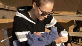 Madre y bebé que se preparan para la fórmula de alimentación que se sienta en banco fotos de archivo libres de regalías