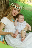 Madre y bebé que se sientan debajo de árbol Fotografía de archivo