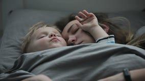 Madre y bebé que toman una siesta junta Una mujer joven con su pequeño hijo está durmiendo en la cama almacen de metraje de vídeo