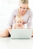 Madre y bebé que usa la computadora portátil Imagenes de archivo