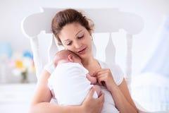 Madre y bebé recién nacido en el cuarto de niños blanco Fotografía de archivo libre de regalías