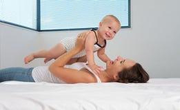 Madre y bebé sonriente lindo que juegan en cama Imagen de archivo libre de regalías
