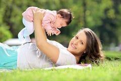Madre y bebé sonrientes en un parque imagenes de archivo