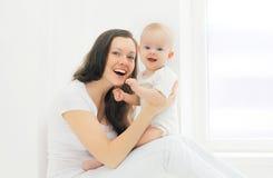 Madre y bebé sonrientes felices en casa en el sitio blanco Fotos de archivo