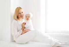 Madre y bebé sonrientes felices en casa en el sitio blanco Imagen de archivo libre de regalías