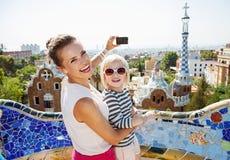 Madre y bebé sonrientes que toman las fotos con la cámara en el parque Guell foto de archivo