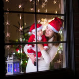 Madre y bebé vestidos como Papá Noel en una ventana en la Navidad Foto de archivo