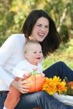 Madre y bebé con las flores - tema de la caída Foto de archivo